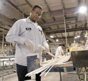 Delwyn Franklin and George Daniel cut fiberglass rods at GlasForms Inc.