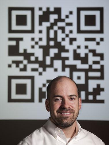 Infomedia's Jason Lovoy said there are several ways companies can use quick-response codes, like the one behind him in the photo, to boost their business.