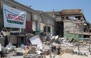 "Krispy Kreme bearing a ""We'll be back"" sign after the killer tornado cut through Tuscaloosa, leaving miles of total devastation."
