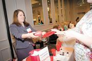 State Farm's Amy Smith networks at her company's exhibition booth during a break between speakers.