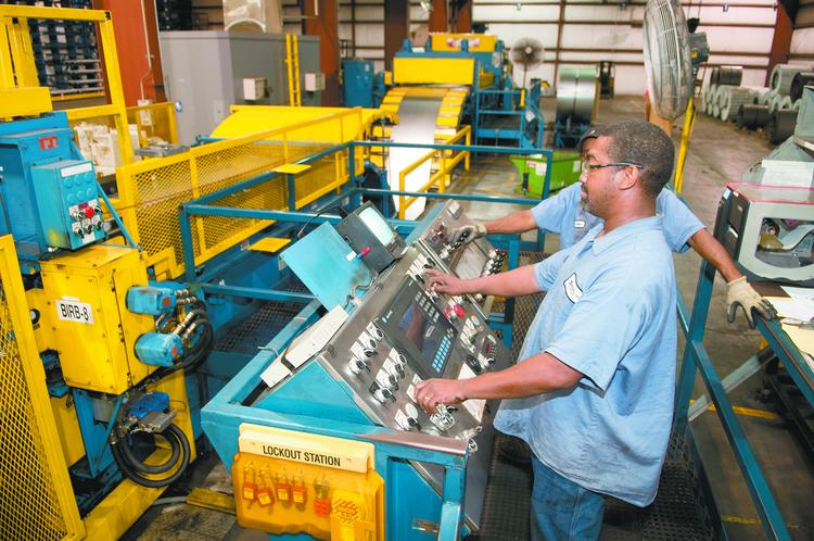 Charles Hines, front, and Dewayne Bryant run a steel cutting machine at O'Neal Flat Rolled Metals. The machine cuts rolled steel into specific lengths. The company is expanding into the Southeast.