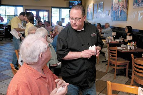Max's Deli's Steve Dubrinsky, right, talks with Bill Vann, a first-time customer, during lunch recently. The eatery has been offering deals through Groupon to get new diners in the door.