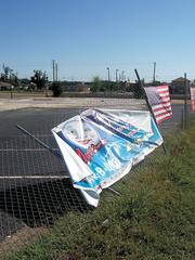 With debris removed, Tuscaloosa's Full Moon restaurant site is still only marked by a restaurant banner and American flag.
