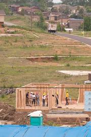 Workers frame a house in Pratt City.