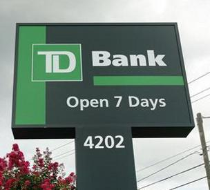 TD Bank branch sign: TD agreed to settle a $62 million class-action lawsuit accusing the bank of overcharging customers on checking account overdraft fees.
