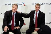 Doug Parker, chief executive officer of US Airways Group Inc., left, speaks 
