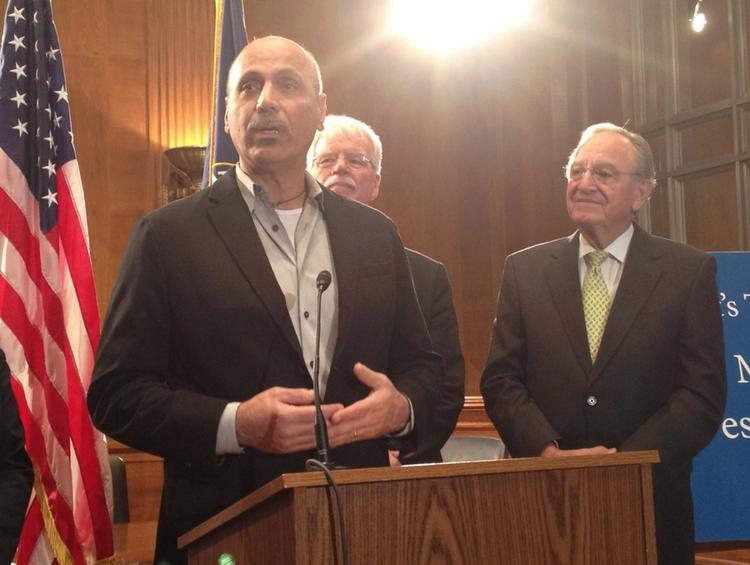 Busboys and Poets restaurant group owner Andy Shallal speaks in favor of raising the minimum wage at a Capitol Hill press conference hosted by Sen. Tom Harkin, right.