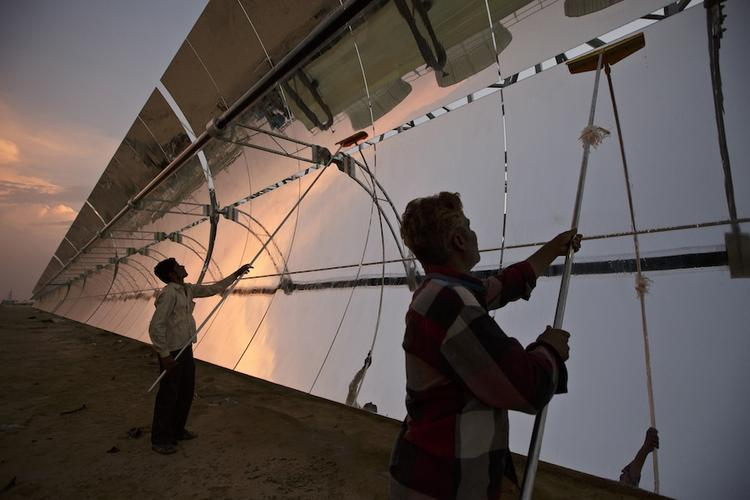Workers clean reflector panels at the Godawari solar-thermal power plant in India; U.S. businesses point to clean energy as one of the industries the Indian government is trying to grow through unfair trade practices.