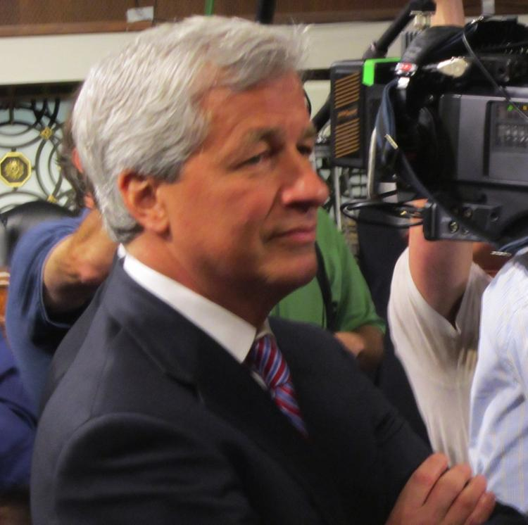 "Jamie Dimon, chairman and CEO of J.P. Morgan Chase, watches as a protester shouts out that he's ""a crook"" at a Senate Banking Committee hearing."