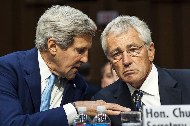 Secretary of State John Kerry confers with Defense Secretary Chuck Hagel at Senate hearing today on whether to authorize a military attack against Syria over its use of chemical weapons.