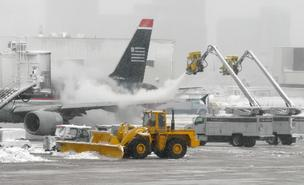 Flight cancellations: Planes being de-iced in a winter storm at Logan International Airport