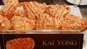 The 'Kai Yong,' a sweet-and-savory, triangular doughnut sold at Dunkin' Donuts in Thailand, combines a traditional glazed doughnut with a topping of dried, shredded chicken and a drizzle of Thai hot sauce.