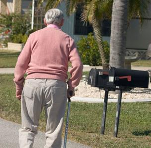 Photo of a senior walking toward a mailbox.