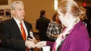 Aaron Gilman of Hinckley, Allen & Snyder demonstrates international diplomacy by presenting his business card to Dara Khan of the British Consulate at the Boston Business Journal's Top 100 Women-Led Businesses breakfast.
