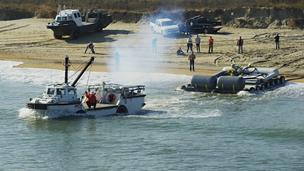 A Resolute Marine Energy wave conversion device is towed into the ocean by a U.S. Army Corps of Engineers amphibious vehicle.