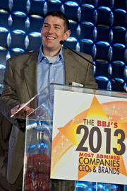 Enservio's Jon McNeill is smiling because: A) He's a happy guy B) He was awarded the BBJ's Most Admired CEO of a midsize company C) By winning, he also won a bet with Harpoon Brewery's CEO Dan Kenary thus getting free beer D) All of the above.