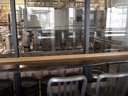 The bar in Harpoon's new beer hall looks out over a keg-filling line and a soon-to-be-installed canning line.