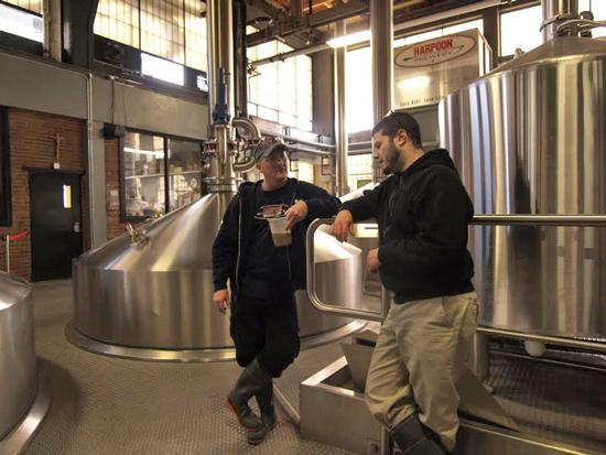 He's not drinking that. Harpoon Brewery workers Chris Jacques and Joe Thomas talk shop in the brew house. A catwalk, currently under construction, will take brewery tours from the new beer hall, across the bottling area, to the brew house. Jacques is holding a wort sample.
