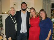 Debi Benoit, left, principal of Benoit Mizner Simon & Co., recently hosted a holiday party at her Wellesley home where guests donated unwrapped toys for donation to Mass General's Hospital for Children. New England Patriot Rob Ninkovich stopped by to chat with guests and sign autographs.