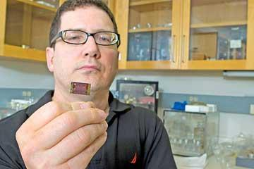 Michael Naughton, Boston College physics professor, shows an up close look at the nanotech-based implant he is working on to treat macular degeneration.