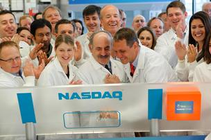 Christoph Westphal, center right, chairman and CEO of Verastem, holds the pen that rings the bell to open Nasdaq on Tuesday morning. Verastem co-founder Robert Weinberg, center, and the company's employees all attended.