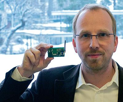 An IBM researcher holds up a MEMSIC component of a developer-friendly  remote sensor network system the two companies partnered to develop.