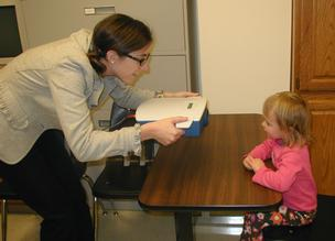 A post-doctoral fellow at the Retina Foundation of the Southwest performs the three-second eye scan with the Pediatric Vision Scanner at a clinical trial site.