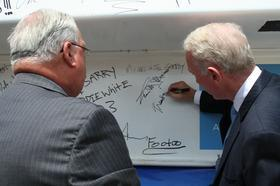 Mayor Thomas M. Menino and developer Joseph Fallon sign the final beam before it was hoisted atop the 18-story Vertex headquarters.