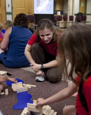 A Museum educator leads a class in an engineering activity where the students build and walk across a Roman arch bridge