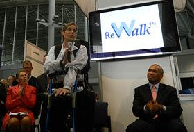 U.S. Army Veteran Theresa Hannigan demonstrates ARGO's ReWalk at the AdvaMed 2012 Massachusetts Pavilion, as Massachusetts Life Sciences Center President and CEO Susan Windham-Bannister, (left) and  Gov. Deval Patrick look on.