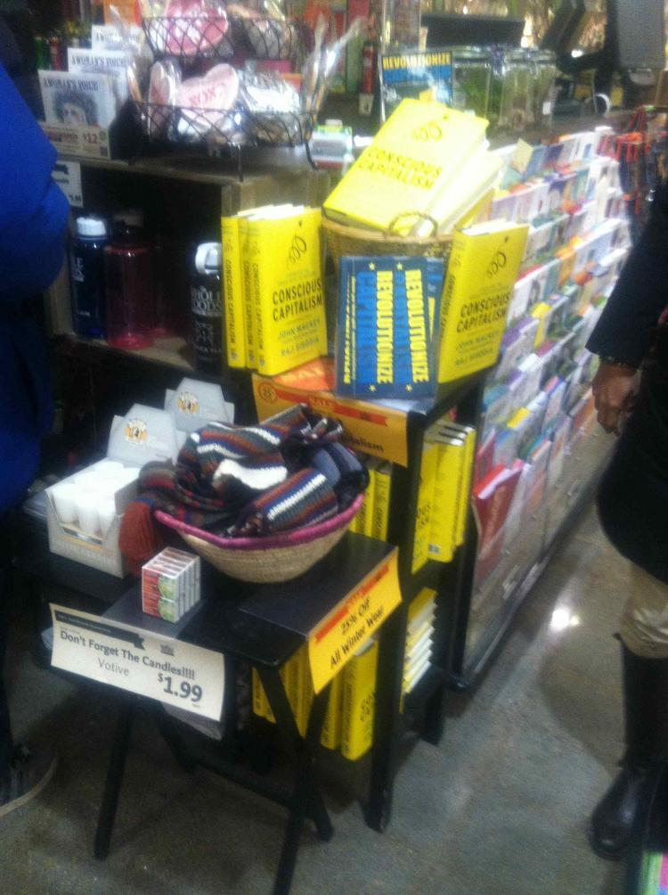 """Copies of John Mackey's book, """"Conscious Capitalism,"""" stacked at a Boston Whole Foods in Jamaica Plain."""
