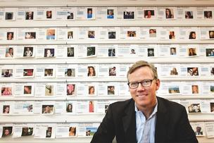 HubSpot CEO and co-founder Brian Halligan sits in front of a wall of profiles of HubSpot employees at the company's Cambridge headquarters. The fast-growing marketing software firm is mulling acquisitions, new venture money and an IPO, Halligan said.