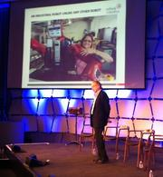 Rodney Brooks speaks at the MIT Emerging Technologies Conference Wednesday, with a projected image of Baxter, the robot produced by his company Rethink Robotics, in the background.