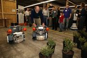 Joe Jones, co-founder of Harvest Automation of Billerica demonstrates a robot used in greenhouse and nursery production that can lift potted plants.