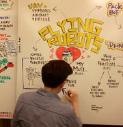 Whiteboards were on display at TEDxBoston featuring points made by presenters during their talks. Here, a host writes a few sayings from the talk by Helen Greiner, former iRobot co-founder and now founder of CyPhy Works.