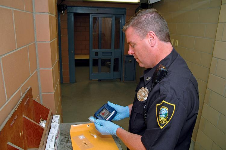 A law enforcement official uses TruNarc to detect oxycodone, also known as Percocets.