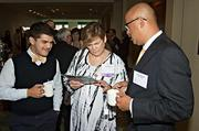 Flanked by her son Cyrus Dahmubed and Richard Muraida honoree Paula Chesbrough of Eagle Bank checks out a vendors brochure at the Mass High Tech & Boston Business Journal's 2013 CIO of the Year awards breakfast.