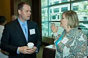 Rich Tobin of Care.com in conversation with Lisa Svensson of Merrill Lynch Wealth Management during the morning coffee hour at the Mass High Tech Women To Watch awards breakfast. Care.com was an event partner and Merrill Lynch a presenting partner of the event.