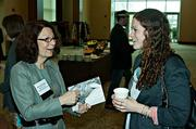 Brenda Magle of Merril Lych Wealth Management shares a laugh with City Year's Julianna Morrall during the morning coffee hour at the Mass High Tech Women To Watch awards breakfast. Merrill Lynch was a presenting partner of the event.