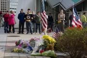 """Dressed in their Boston garb, visitors at the makeshift memorial of slain MIT Officer Sean Collier console one another. MIT Chancellor Eric Grimson in a letter to the MIT community said Collier was an """"extraordinary young man, an excellent police officer and a truly beloved member of our community."""""""
