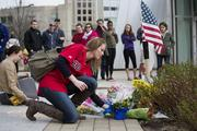In a letter to the MIT community Chancellor Eric Crimson said that while there is a sense of relief that order has been restored, they have now turned to mourn Officer Collier and victims of the bombings. Here a woman places flowers at the site in front of MIT's Stata Center where Collier was shot. In the plant is a note thanking him.