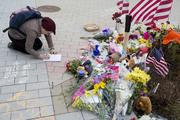 A woman kneels at the makeshift memorial of MIT Officer Sean Collier to write a note to add to the many notes of thanks written in chalk on the pavement and in other memorabilia left behind at the site where Collier was killed by the alleged Boston Marathon bombers.