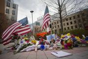 """Two American flags serve as the backdrop to MIT Police Officer Sean Collier's makeshift memorial where people have left flowers, notes of thanks and filled entries in a notebook left at the site. MIT Chancellor Eric Grimson said MIT is planning a """"major campus event"""" this week."""