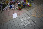 'Thank You -- Boston Strong -- Tufts' is written in chalk at the makeshift memorial for Wilmington native and Somerville resident Sean Collier, an MIT Police Officer who was killed by the alleged Boston Marathon bombers.