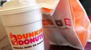 Photo of a coffee cup and a bag bearing the Dunkin' Donuts label.