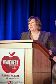 Cheryl Burke, partner and COO at DiCicco, Gulman & Company, accepts their award in the small company category at the Boston Business Journals Healthiest Employers awards breakfast.