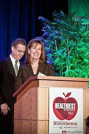 Kristine Martel, director of human resources at Tufts Health Plan accepts their award in the large company category at the Boston Business Journals Healthiest Employers awards breakfast.