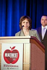 Lois Farkas, vice president of human resources at NEI accepts their award in the medium company category at the Boston Business Journals Healthiest Employers awards breakfast.