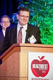 Owen Bourke, associate director, administrative and site services of Shire Human Genetic Therapies accepts their award in the large company category at the Boston Business Journals Healthiest Employers awards breakfast.