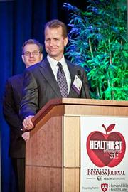 Rand Currier, COO at Granite LLC accepts their award in the large company category at the Boston Business Journals Healthiest Employers awards breakfast.